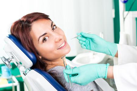 Lächelnde Frau am Zahnarzt sitzt in Zahnarztstuhl bereit für eine zahnärztliche Check-up.