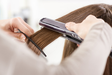 Hairdresser straightening long brown hair with hair irons. photo