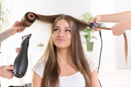 Hairdressers straightening long brown hair with hair dryer and round brush and hair irons. photo