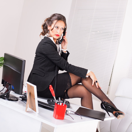 Attractive coquettish secretary sitting on desk and talking on the phone. photo