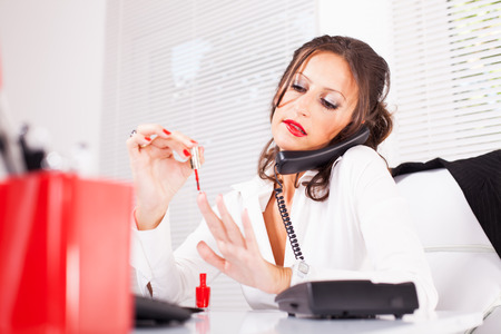 Attractive sexy secretary lacquered nails  in the office and talking on the phone and biting lips. photo