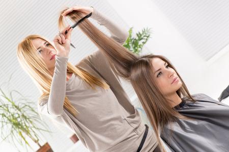 Junge schöne Frau in einem Friseursalon, die ihre Haare schneiden beim Friseur.