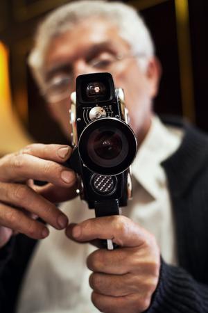 camara de cine: Hombre mayor que sostiene la antigua c�mara de cine. Foto de archivo
