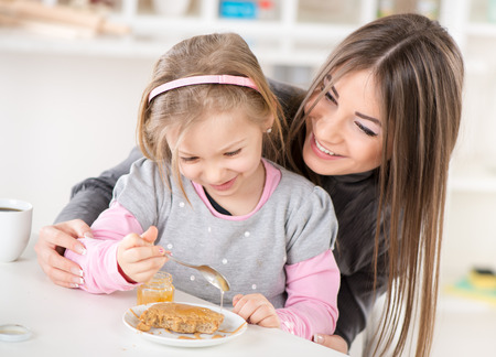 Mother and daughter preparing breakfast eating smear honey over the peanut butter on bread. Stock Photo - 26324739