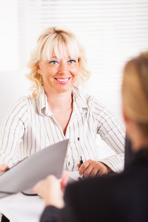 deal in: Friendly business women conducting deal in office