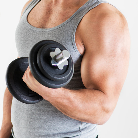 Young muscular man lifting the weights with biceps exercise. Close-up. Stock Photo