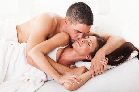 Young guy kissing his girl on the cheek for good morning in the bed. photo