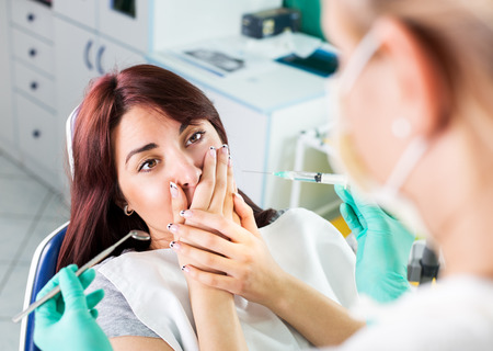 Young female dentist giving anesthesia to the patient before dental surgery. The patient in fear holds hands over mouth. Selective focus, focus on the patient.