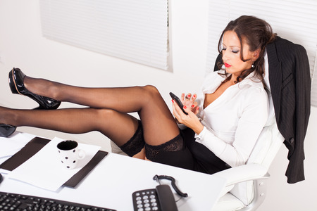 Hot business woman sitting in the office with legs on the table and using mobile phone photo