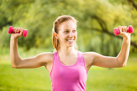 Portrait of Beautiful young woman exercising with weights in the park. photo