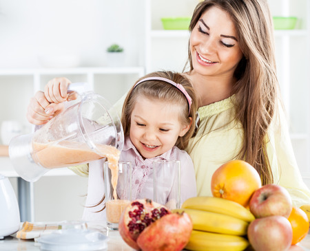 Beautiful young woman and cute little girl pouring juice from blender in the glass. In the kitchen concept.