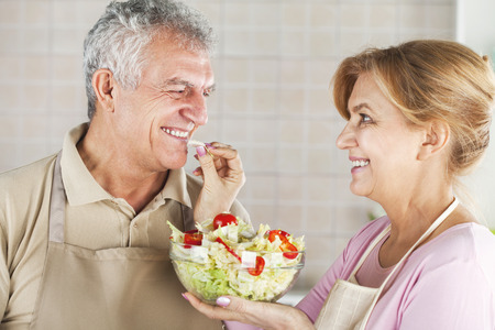 Happy Senior Couple eating salad in the kitchen, and have a fun. photo