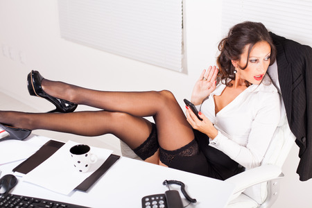 Hot business woman sitting in the office with legs on the table, typing sms on mobile phone with surprised looking photo