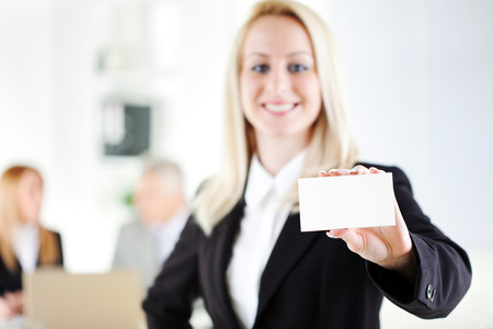 Beautiful young businesswoman holding Blank business card in the office. Looking at camera. Selective Focus, focus on card. photo