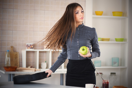 Businesswoman in the kitchen getting ready for work. She is rushing for work. Holding a bag with laptop in one hand and apple in other. photo