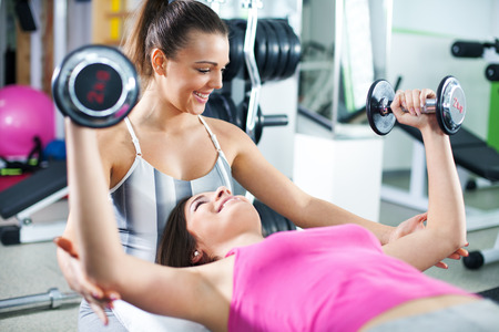 woman chest: Cute Sporty young woman doing exercise in a fitness center with her personal coach. She is working exercises to strengthen her chest.