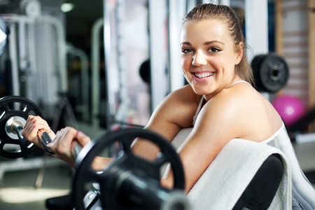 woman lifting weights: Cute Sporty young woman doing exercise in a fitness center. She is working exercises to strengthen her bicep.