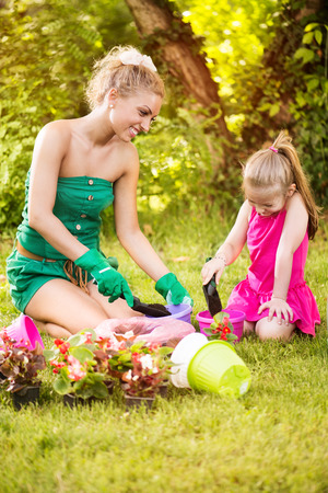 Beautiful mother and daughter planting flowers in the garden. photo