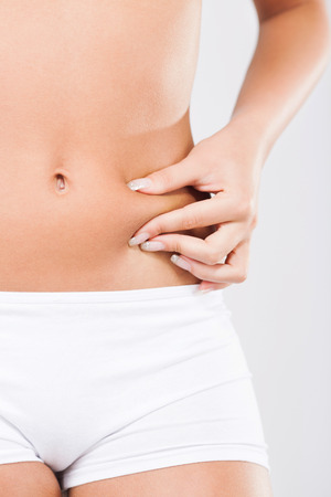 pinching: Young woman pinching waist and checking her body fat. Stock Photo