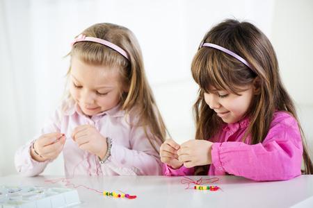 cute little girls: Dos ni�as lindas que hacen joyer�a del grano en el pa�s. Foto de archivo