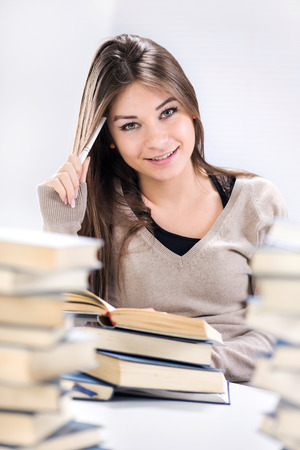 home schooling: Beautiful Student girl learning and thinking between many books. Selective focus. Stock Photo