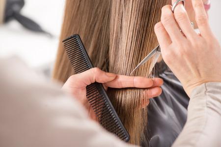 Hairdresser cut hair of a woman. Close-up.