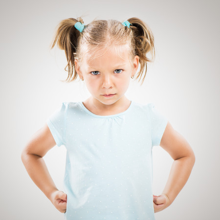 Cute angry little girl standing with hands on hips.