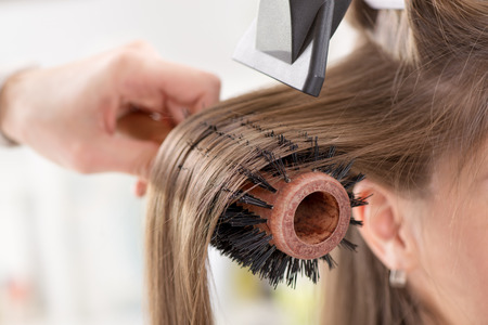 Drying long brown hair with hair dryer and round brush. Close-up. Archivio Fotografico