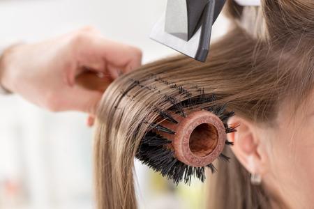 secador de pelo: Secar el pelo largo de color marrón con secador de pelo y cepillo redondo. Close-up. Foto de archivo