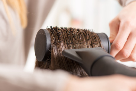 Drying long brown hair with hair dryer and round brush. Close-up. photo