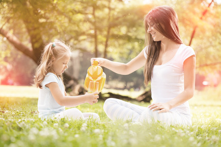 Beautiful Mother and daughter in the nature having little picnic. photo