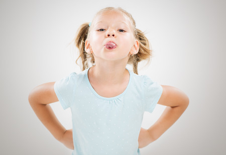 Cute little girl standing with hands on hips and sticking out tongue. photo