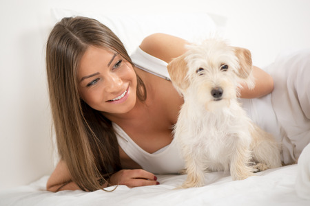 Young beautiful woman and her dog resting in bed photo