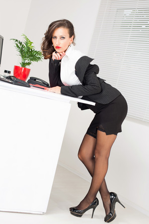 Sexy business woman standing and Leaning on the office table. photo