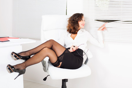 Sexy business woman sitting on office chair and peek through the window. photo