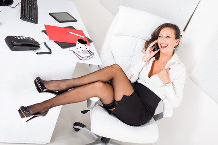 Sexy business woman sitting on office chair and talking on mobile phone. photo