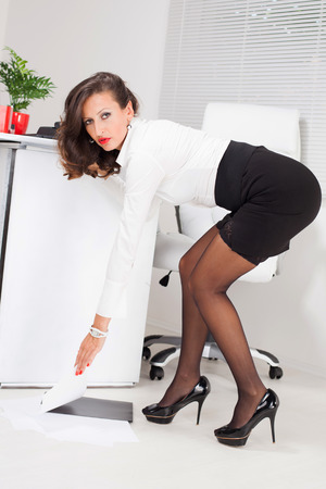 Hot business woman picking up some documents. photo
