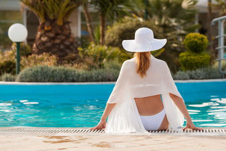 Young beautiful woman enjoying the sun and sitting on edge of the pool.