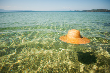 sun hat: Straw sun hat float in the transparent seawater. Stock Photo