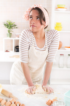 conceived: Conceived young woman making dough in the kitchen