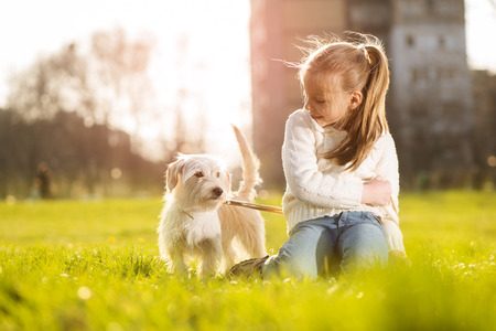 Little girl relaxing with her puppy dog in the park