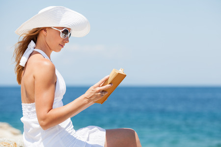 Young beautiful woman reading book and relaxing on the beach. photo