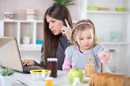 Overworked Business Woman and her little daughter in the morning. Mother read mail and make phone calls before going to work. Daughter smearing peanut butter on bread.