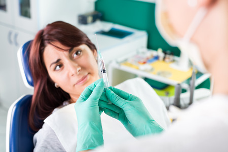 expressing negativity: Young female dentist giving anesthesia to the patient before dental surgery. The patient in fear Expressing Negativity. Selective focus, focus on the patient.
