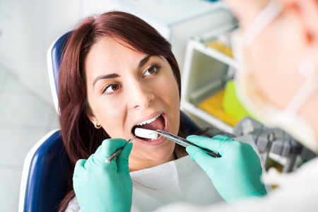 Female dentist preparing patient for a dental treatment. She is inserting cotton pad in patient mouth. Selective focus, focus on the patient. photo