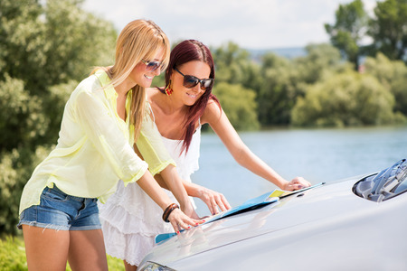 Young women with a tourist map looking for directions. photo