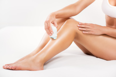 electric razor: Shaving leg with Electric Razor.  Stock Photo