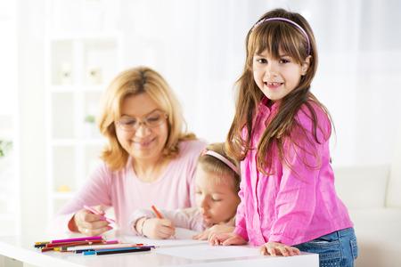 cute little girls: Dos ni�as lindas de dibujo con l�pices de colores en casa con la abuela
