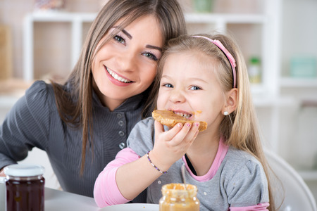 Mother and daughter breakfast in the kitchen. Cute little girl eats bread with peanut butter. Looking at Camera.