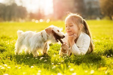 어린 소녀: 어린 소녀가 공원에서 그녀의 강아지와 함께 연주 스톡 사진